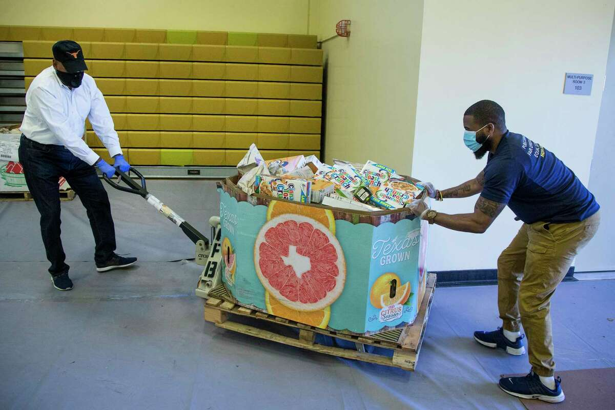 Harris County Commissioner Rodney Ellis, left, and Lawrence Battle roll a pallet of dry goods into the gym at the Julia C. Hester House recreation center on Thursday, April 16, 2020 in Houston. The county is teaming with the Houston Food Bank to provide food to residents impacted by coronavirus. The initiative will allow the food bank to give hundreds of thousands of pounds of food to people who are in need during the pandemic.