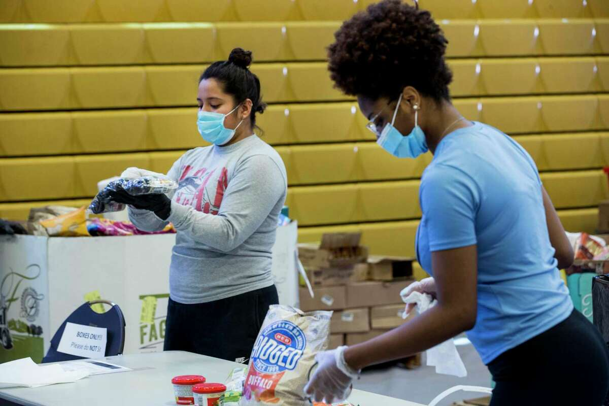 Brendalee Muñoz, let, and Latorea Manuel sanitize and sort dry goods on Thursday, April 16, 2020 at the Julia C. Hester House recreation center in Houston. Harris County is teaming with the Houston Food Bank to provide food to residents impacted by coronavirus. The initiative allows the food bank to give hundreds of thousands of pounds of food to people who are in need during the pandemic.