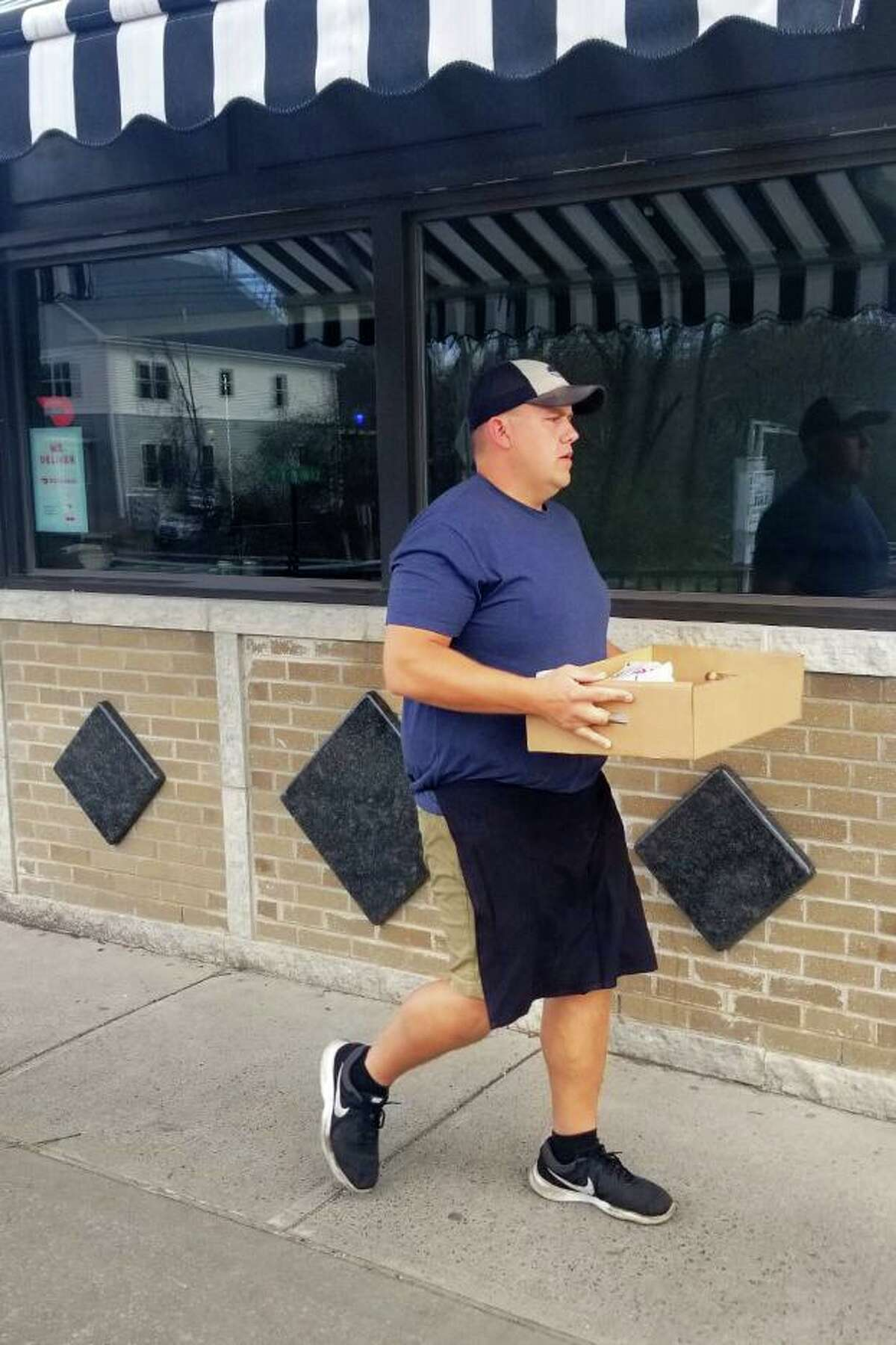 An employee of Illiano's Ristorante and Pizzeria in Middletown leaves the eatery with food for health care workers. Owner Vincent Scileppi is matching every $10 donation from the public to fund the effort. The first week, $700 came in, enough to fund $1,400 worth of pies.
