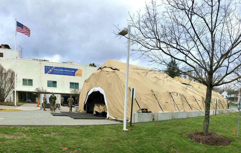 Members of Governor Ned Lamont's Foot Guard and Horse Guard, along with the Connecticut National Guard, construct a 25-bed mobile field hospital on the campus of Sharon Hospital April 10. Photo: Sharon Hospital / Contributed Photo