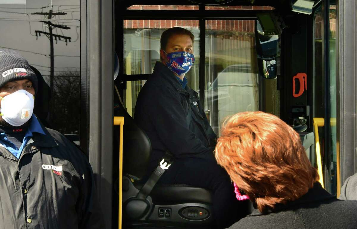 Albany Mayor Kathy Sheehan talks to bus driver Josh Richards, in seat, as CDTA bus drivers participate in the ?'Sound the Horn?