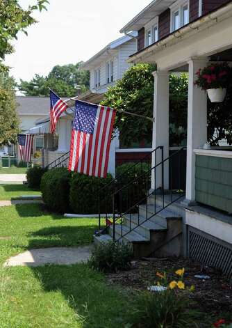 A Row Of American Flags Hang From Houses In Williamsport