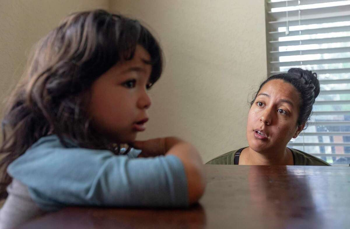 Kimberly Rosales, right, talks to her youngest daughter, 4-year-old Scarlet, about choices Scarlet can make after Scarlet became frustrated with an art project she was doing. Like many, the Rosales family is adjusting to everyone being home most of the time due to the stay-at-home orders issued by the city to stop the spread of the coronavirus.