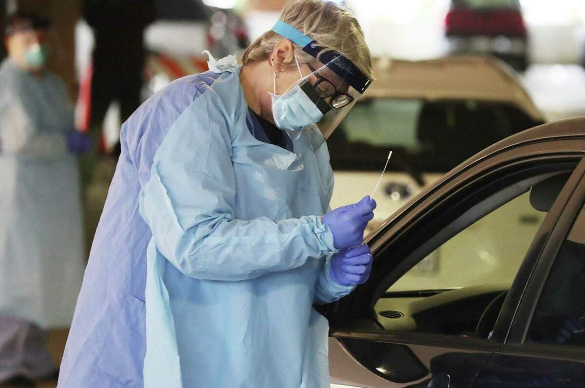 A nurse collects a nasal swab sample from a University of Washington Medicine employee in their car in Seattle.