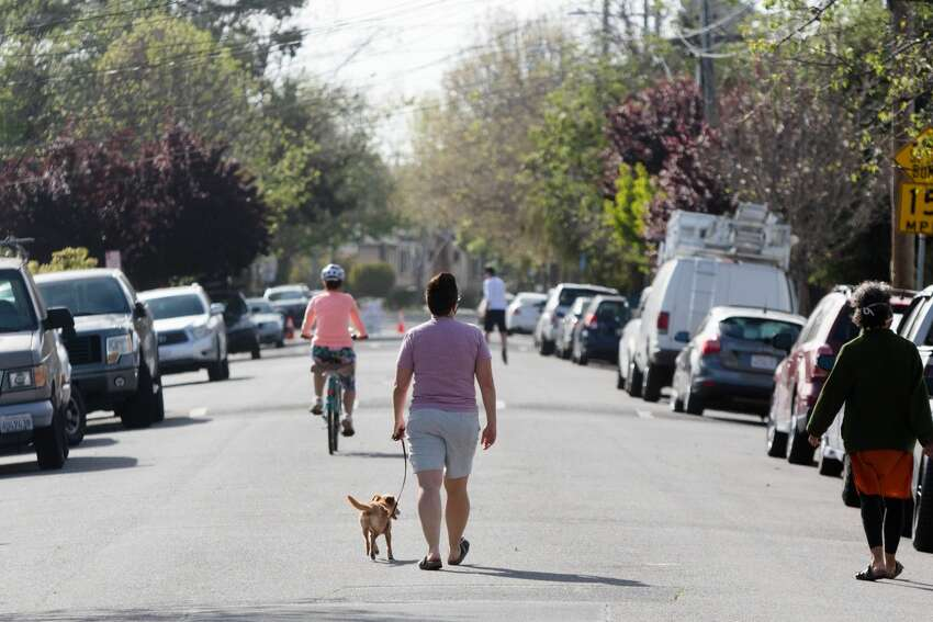 People walk and ride bikes down 42nd Street in Oakland, Calif. on April 15, 2020. The city's