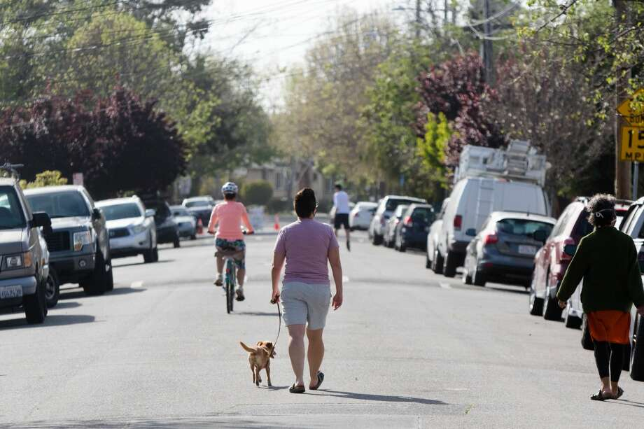 "People walk and ride bikes down 42nd Street in Oakland, Calif. on April 15, 2020. The city's ""slow street"" program started with four streets, where signs, barricades and cones were placed to signify the soft closure of the street for pedestrian and to encourage physical activity. Photo: Douglas Zimmerman/SFGate / SFGate"