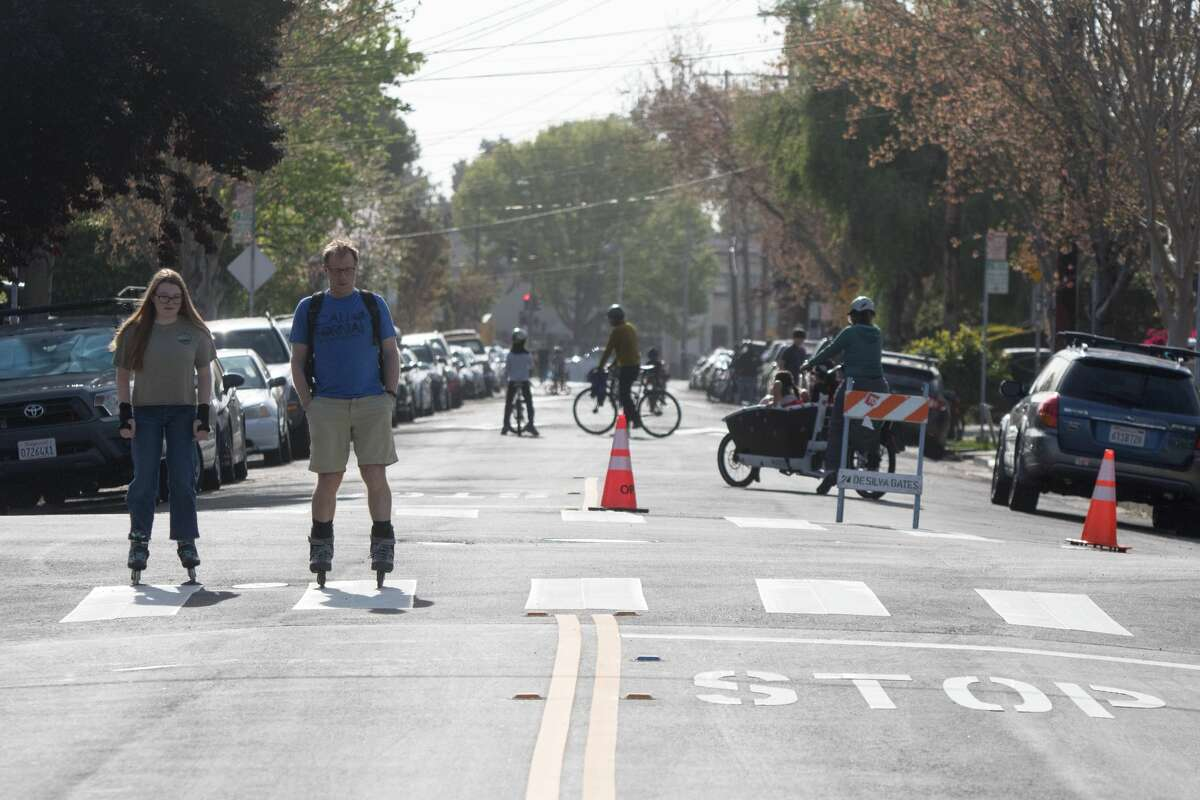 """People skate and ride bikes down 42nd Street in Oakland, Calif. on April 15, 2020. The city's """"slow street"""" program started with four streets, where signs, barricades and cones were placed to signify the soft closure of the street for pedestrian and to encourage physical activity."""