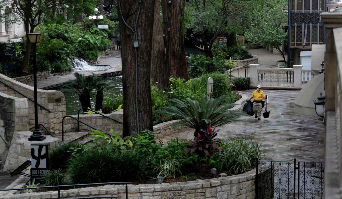 A worker wipes down handrails and other surfaces along the mostly empty River Walk in San Antonio, Monday, March 30, 2020. Due to the COVID-19 outbreak, San Antonio an many other Texas cities are under stay at home orders. (AP Photo/Eric Gay)