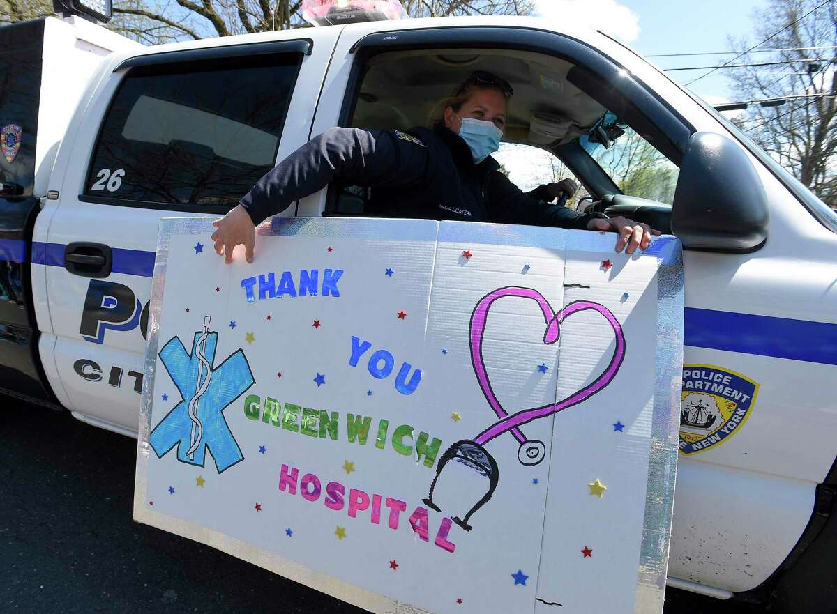 A Rye, New York police unit thanks hospital workers, as they wave and cheer outside Greenwich Hospital as first responders pass by in a caravan of lights and sirens in Greenwich, Connecticut on April 16, 2020. The first responders arrived in police vehicles, EMS ambulances, and fire department trucks to give thanks to healthcare workers for their efforts in combating the coronavirus (COVID-19) pandemic.