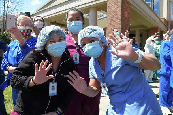 Hospital workers wave and cheer outside Greenwich Hospital as first responders pass by in a caravan of lights and sirens in Greenwich, Connecticut on April 16, 2020. The first responders arrived in police vehicles, EMS ambulances, and fire department trucks to give thanks to healthcare workers for their efforts in combating the coronavirus (COVID-19) pandemic.