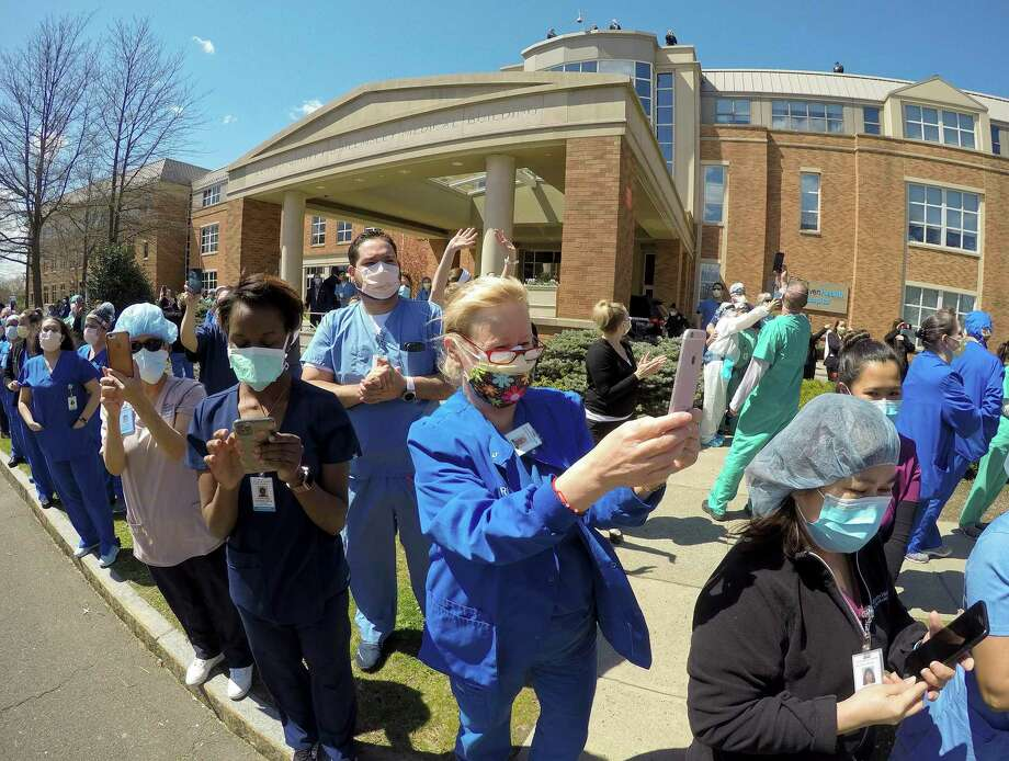 Hospital workers wave and cheer outside Greenwich Hospital as first responders pass by in a caravan of lights and sirens in Greenwich, Connecticut on April 16, 2020. The first responders arrived in police vehicles, EMS ambulances, and fire department trucks to give thanks to healthcare workers for their efforts in combating the coronavirus (COVID-19) pandemic. Photo: Matthew Brown / Hearst Connecticut Media / Stamford Advocate