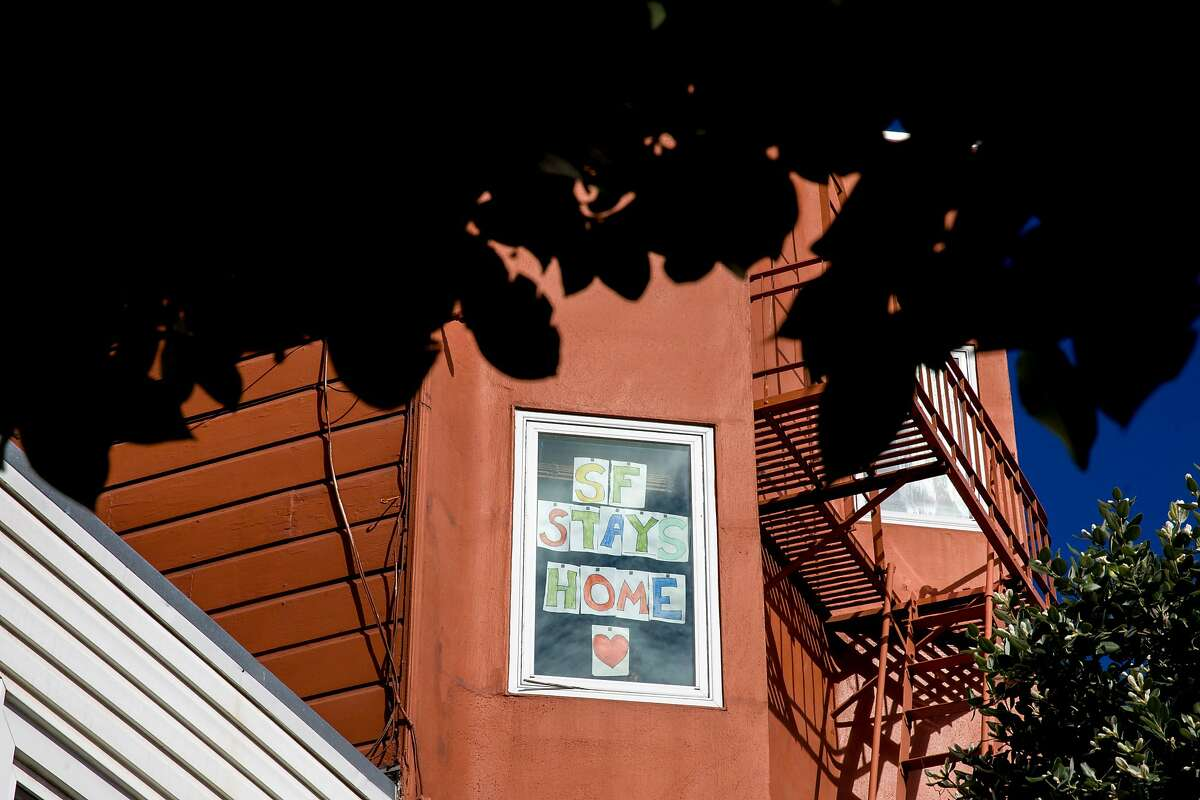 """A sign in Erin Cox's window reads """"SF Stays Home"""" near Dolores Park in San Francisco, Calif. Wednesday, March 25, 2020. Seven counties in the Bay Area have been ordered to shelter in place in an attempt to prevent the spread of the Coronavirus."""