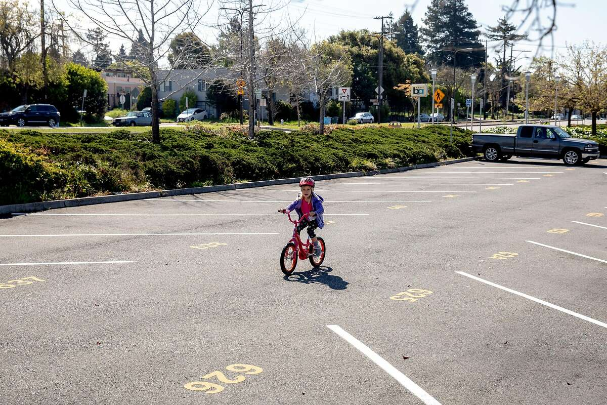Jasmine Gleason, 7, rides her bike through an empty parking lot at North Berkeley BART Station in Berkeley, Calif. Tuesday, April 7, 2020. With schools and workplaces closed through the shelter-in-place order, parents are getting creative with entertaining their children through the day and public transit has seen a decline in ridership, leaving its parking lot open for bike riding and other recreation.
