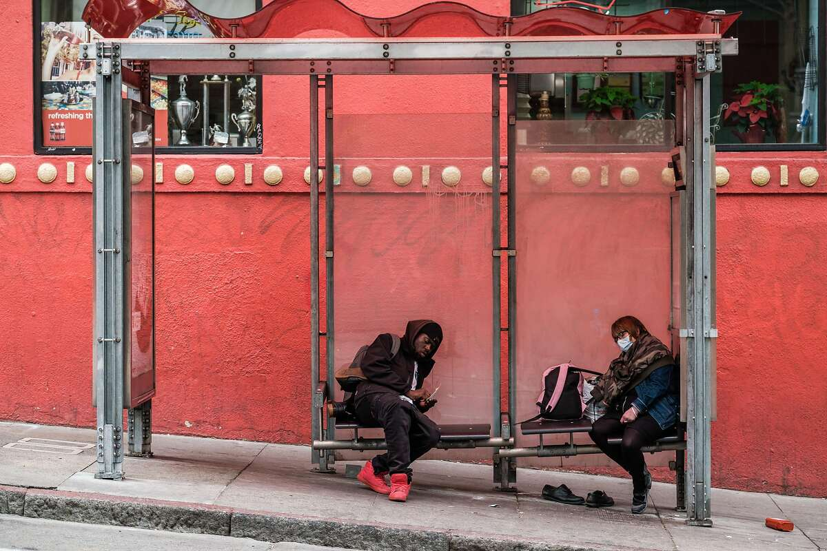 People huddle at a bus stop in San Francisco, Calif. on Monday, March 23, 2020.
