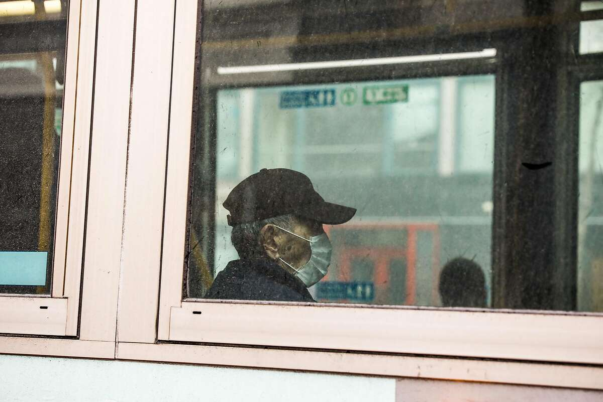A MUNI passenger wears a mask while driving on Market Street during the second week of shelter in place orders due to the coronavirus on Sunday, March 29, 2020 in San Francisco, California.