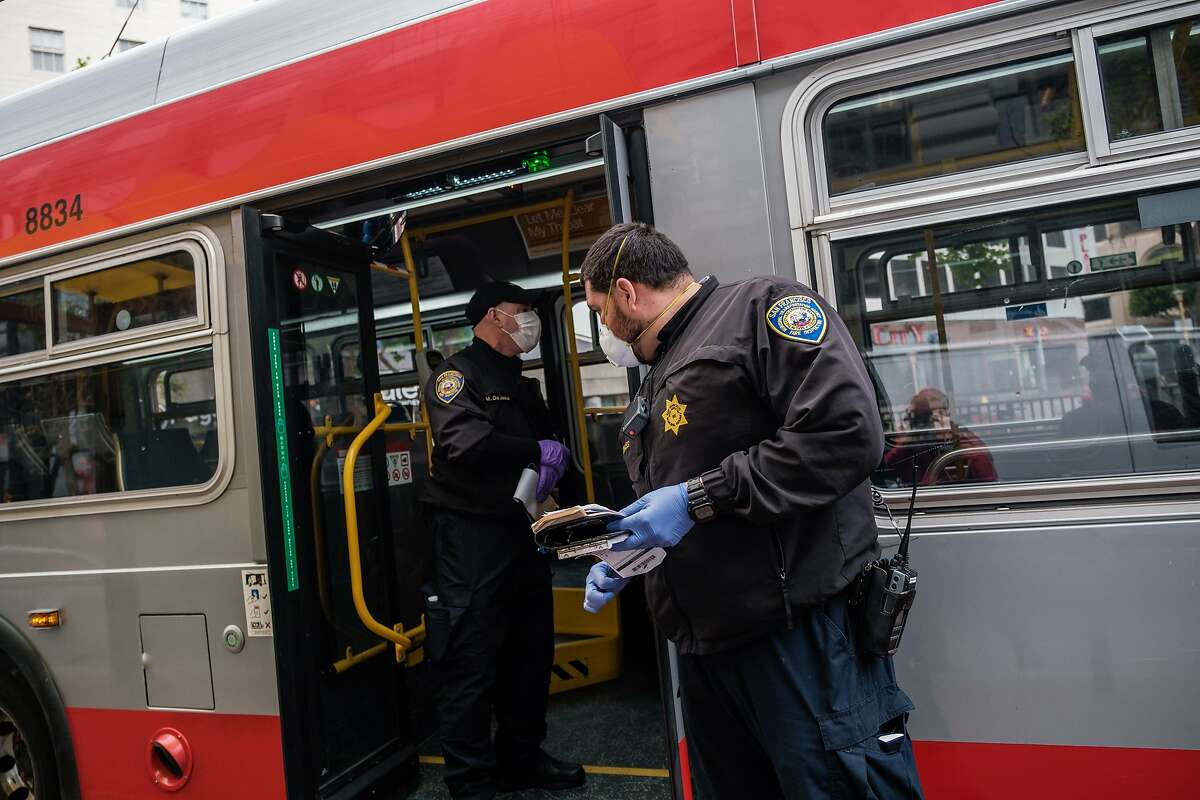 MTA traffic fare inspectors Herman Morales, right, and Mark DeJesus, left, prepare to board a bus and check on the occupancy, social distancing and number of people wearing masks on the bus in San Francisco, Calif. on Thursday April 16, 2020.