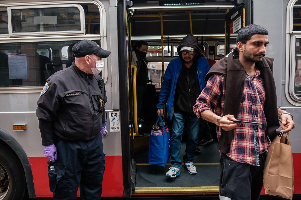 MTA traffic fair inspector Mark DeJesus checks a bus for occupancy, social distancing, and number of people wearing masks on a bus in San Francisco, Calif. on Thursday April 16, 2020.