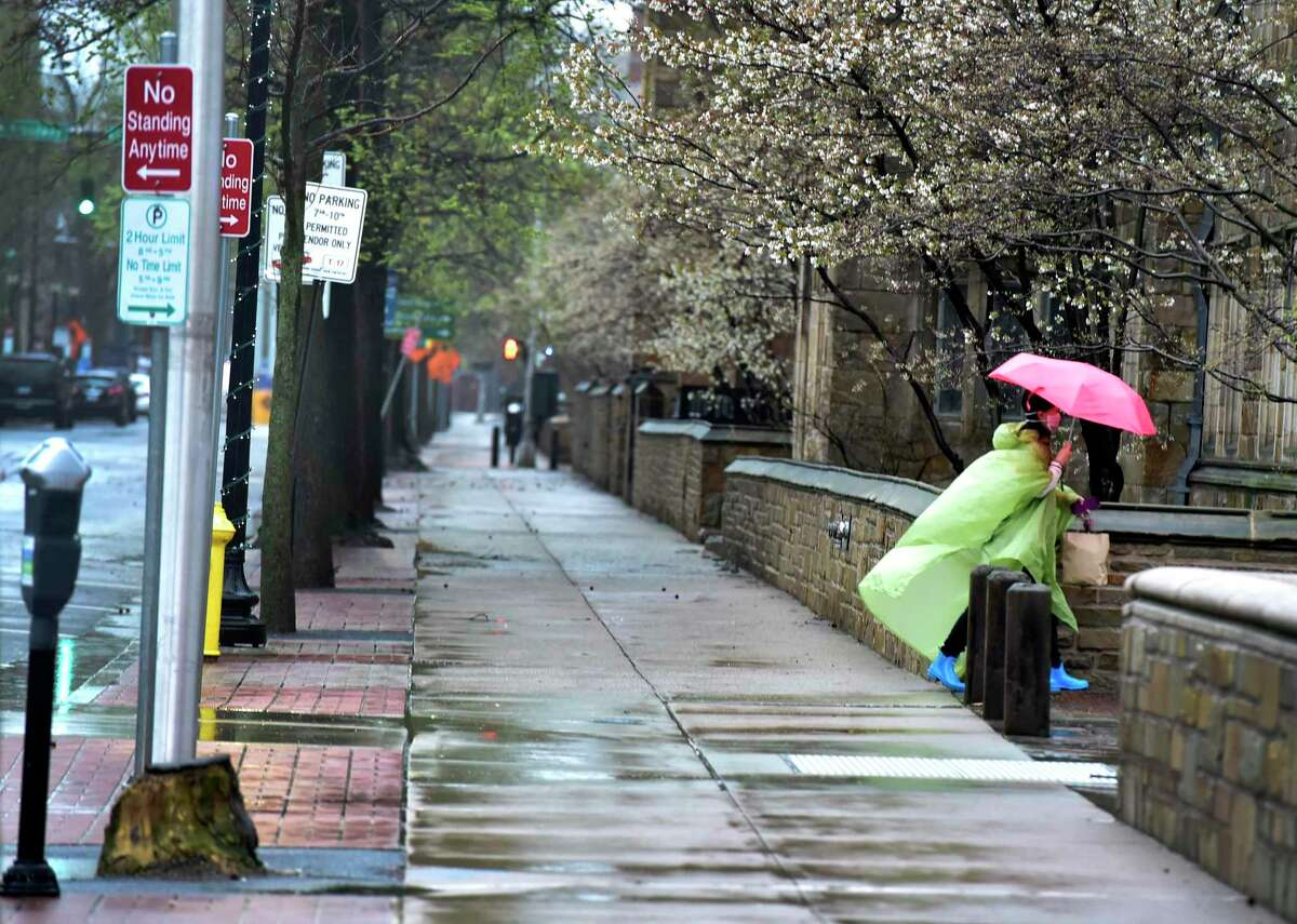 A woman walks in the rain on an empty York Street in New Haven on Monday, April 13, 2020. Connecticut's labor department reported that the state lost jobs in March 2020 and saw its unemployment jump to
