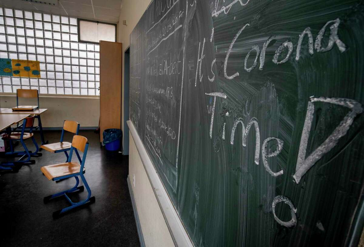FILE -- In this Friday, March 13, 2020 photo a slogan on a chalkboard reads 'It's Corona Time' in an empty class room of a high school in Frankfurt, Germany, March 13, 2020. Germany plans to let smaller shops reopen next week after a weeks-long coronavirus shutdown and to start reopening schools in early May, but Europea€™s biggest economy is keeping strict social distancing rules in place for now. (AP Photo/Michael Probst, file)
