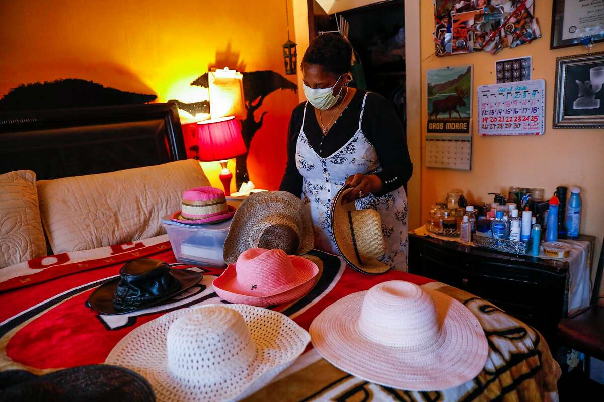 Natalie Henry Berry the daughter of Tessie Henry who died of Covid-19 at the age of 83 looks through her mothers collection of hats on Saturday, April 11, 2020 in San Francisco, California.