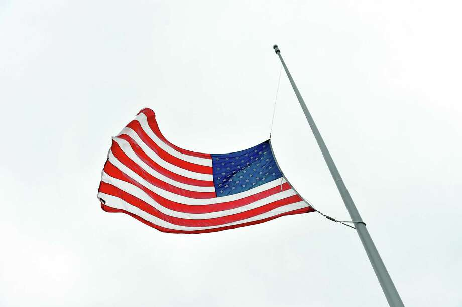 The United States flag is flown at half-staff in front of the Big Y grocery store in Shelton as directed by Governor Ned Lamont for those who have lost their lives or been affected by COVID-19 on April 13, 2020. Photo: Arnold Gold / Hearst Connecticut Media / New Haven Register