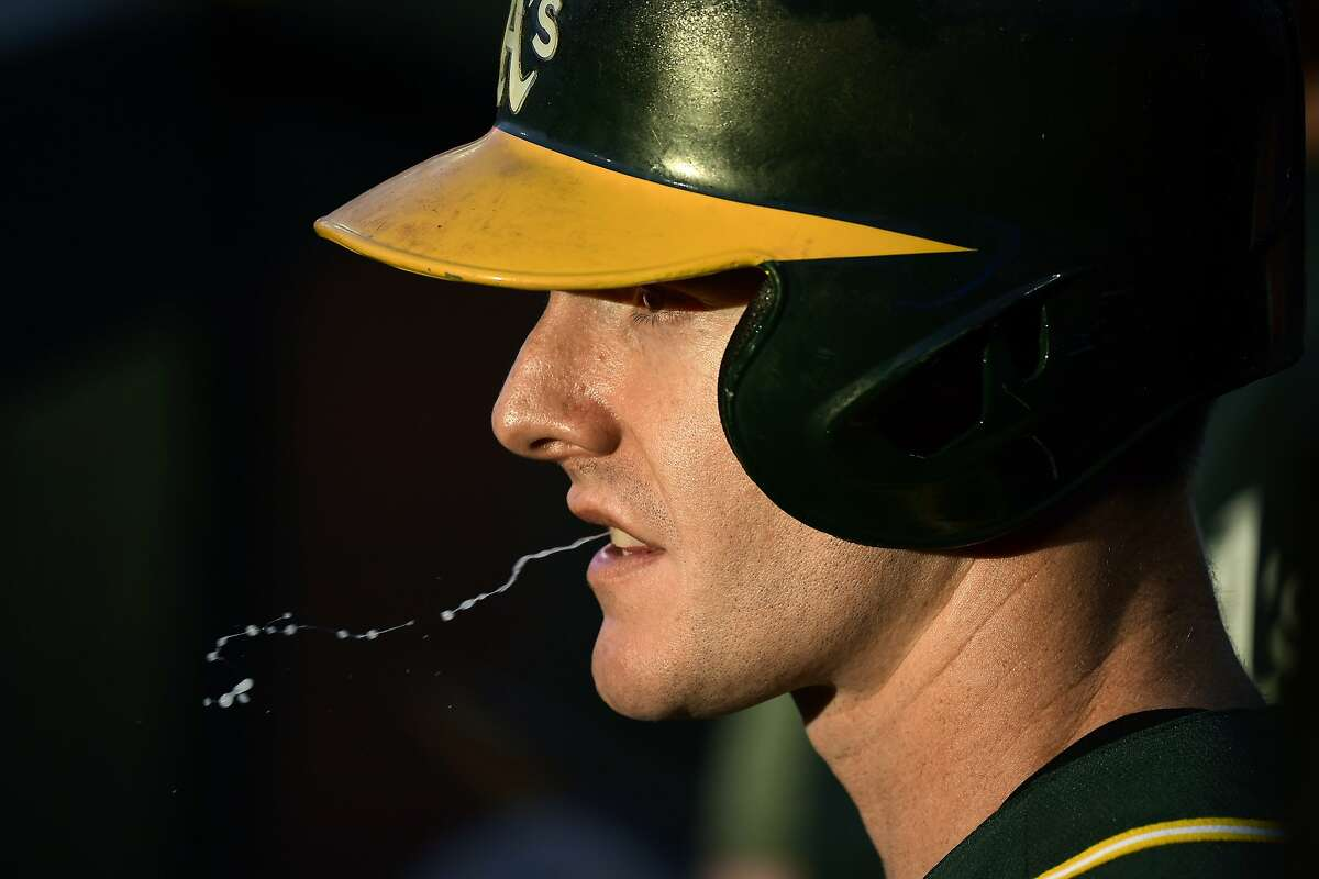 Oakland Athletics' Mark Canha spits as he waits to bat during the first inning of the team's baseball game against the Los Angeles Angels on Thursday, June 27, 2019, in Anaheim, Calif. (AP Photo/Mark J. Terrill)