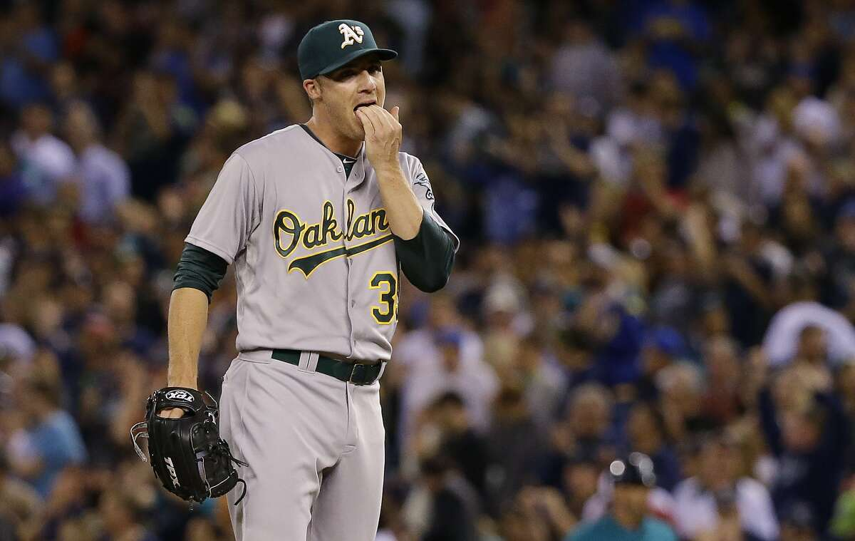 Oakland Athletics pitcher Eric O'Flaherty licks his fingers after he gave up a solo home run to Seattle Mariners' Kendrys Morales in the sixth inning of a baseball game, Friday, Sept. 12, 2014, in Seattle. (AP Photo/Ted S. Warren)
