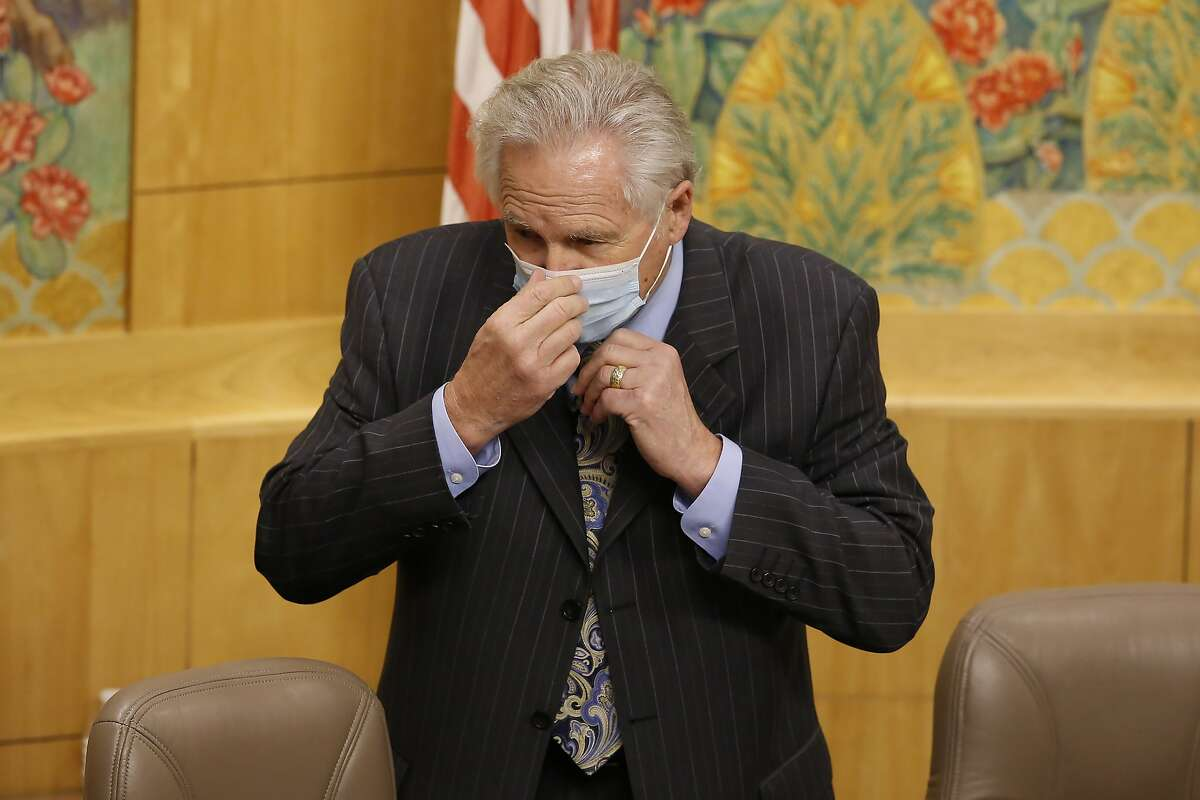 State Sen. Jim Nielsen, R-Gerber, vice chair of senate budget committee, puts on a face mask before the start of a hearing of the special subcommittee on COVID-19, at the Capitol in Sacramento, Calif., Thursday, April 16, 2020. Lawmakers are looking into how Gov. Gavin Newsom has been spending money to address the new coronavirus crisis. Following social distancing procedures, only Nielsen and Sen. Holly Mitchell, D-Los Angeles, chair of the budget committee, attended the hearing in person while other committee members joined by video. (AP Photo/Rich Pedroncelli, Pool)