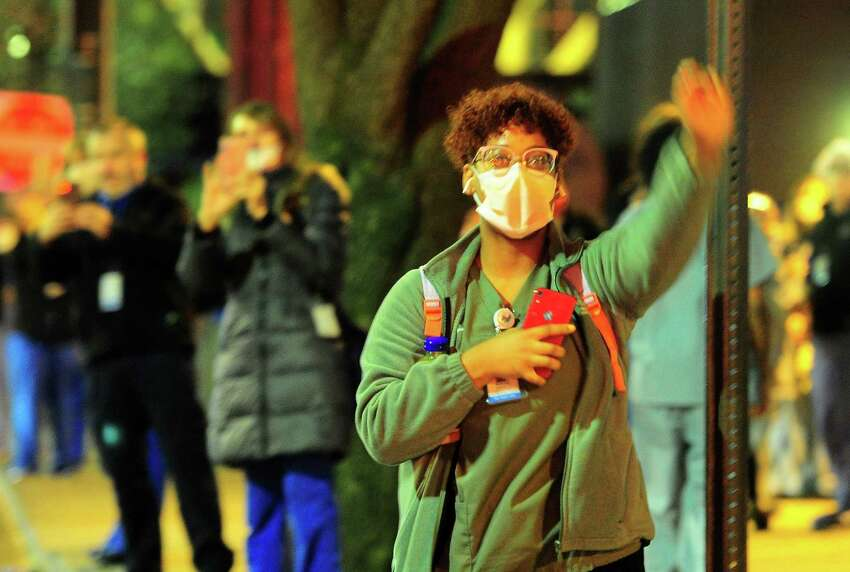Yale New Haven Hospital health care worker Marlene Montilla wave as dozens of first responders drive past to thank them for their hard work fighting the coronavirus pandemic in New Haven, Conn., on Thursday Apr. 16, 2020.