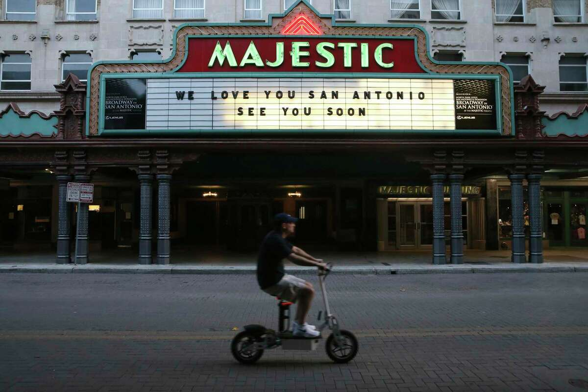 A scooter rider drives past the Majestic Theatre, shut down during in compliance with the stay-at-home ordinance. Columnist Michael Taylor writes that the current bailout has highlighted the American tendency to attach moral failure and moral conditions to financial need and poverty.