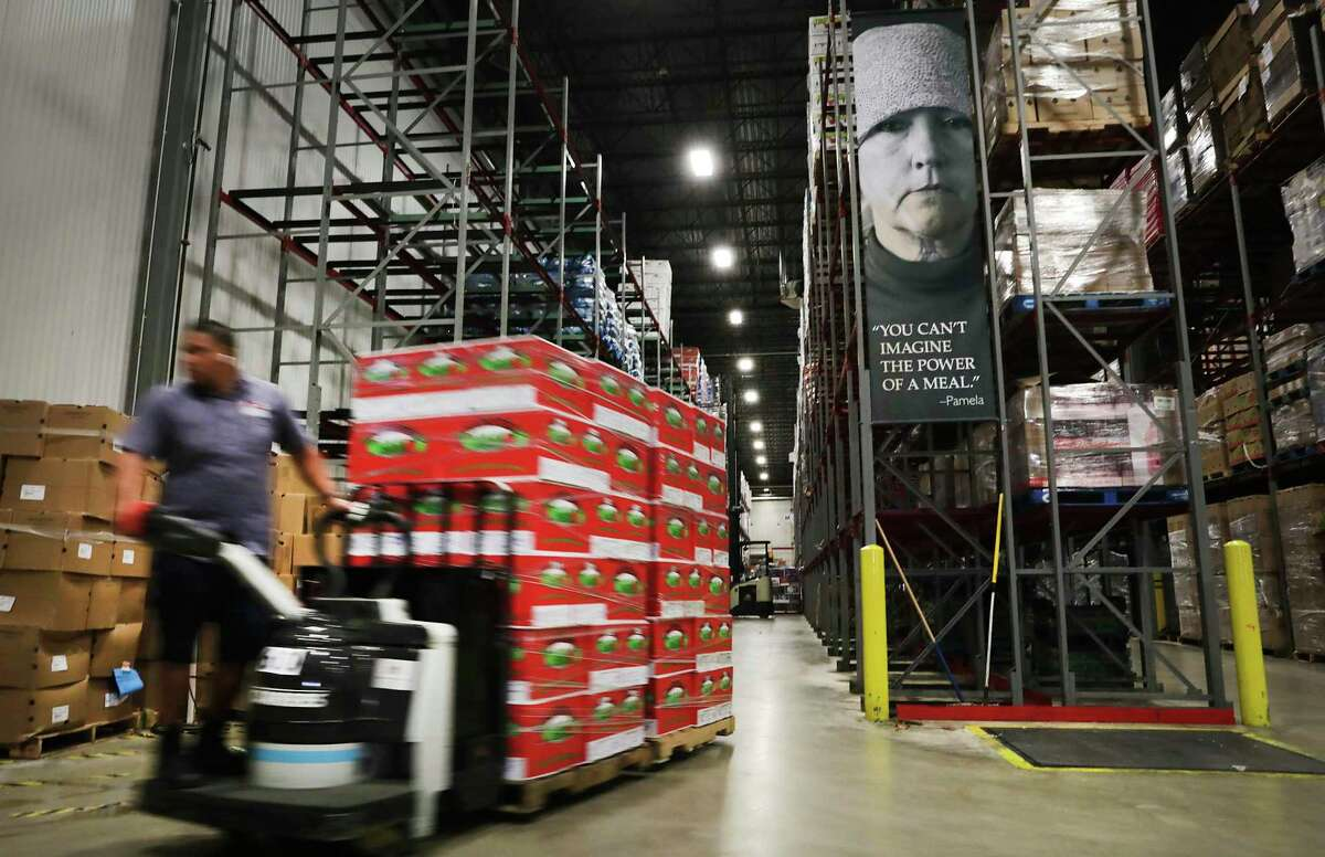A load of apples is prepped at the San Antonio Food Bank to be loaded onto trucks Thursday, April 16, 2020, and delivered to the Alamodome for a drive-through emergency food distribution on Friday.