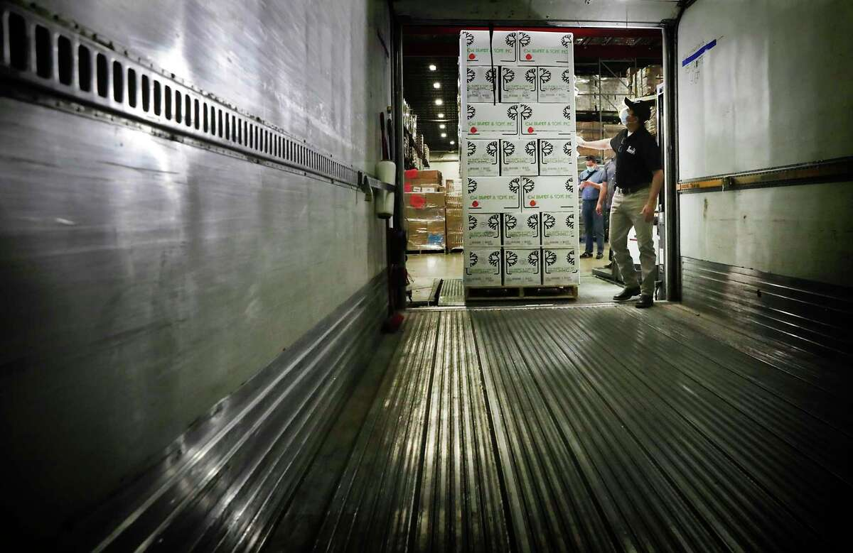 David Carvajal, warehouse manager at the San Antonio Food Bank, checks the height of a load of apples before trucks are filled on Thursday, April 16, 2020, in preparation for an emergency food distribution at the Alamodome on Friday.