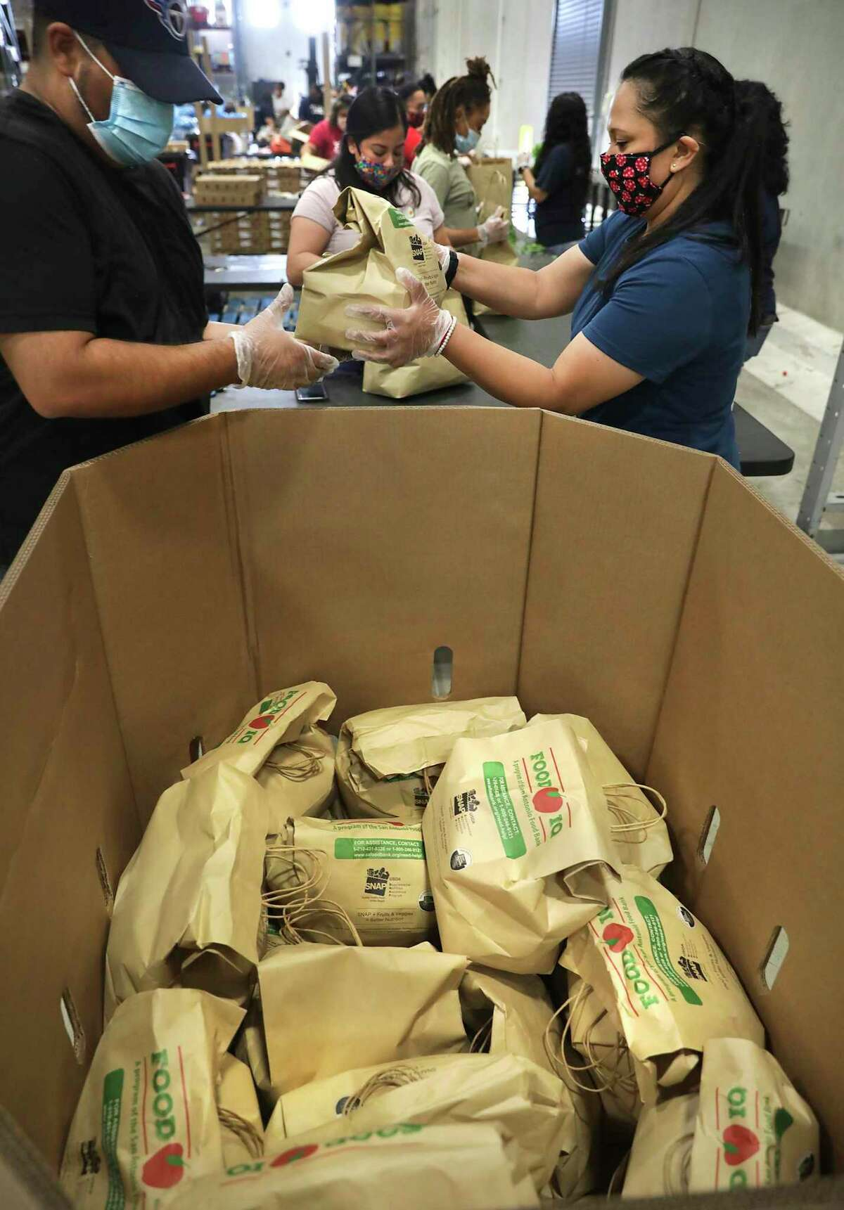 Volunteers from Pre-K for SA load bags of produce at the San Antonio Food Bank on Thursday, April 16, 2020, in preparation for an emergency food distribution at the Alamodome on Friday.