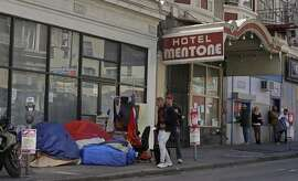 Pedestrians walk to the edge of the sidewalk to avoid stepping on people in tents and sleeping bags on Monday, April 13, 2020, in the Tenderloin area of San Francisco. Local governments have begun moving large numbers of homeless into hotels as part of Operation Roomkey. Among the requirements are that people get tested when they check in and that medical staff at the hotel make regular checks to see if people's conditions change.