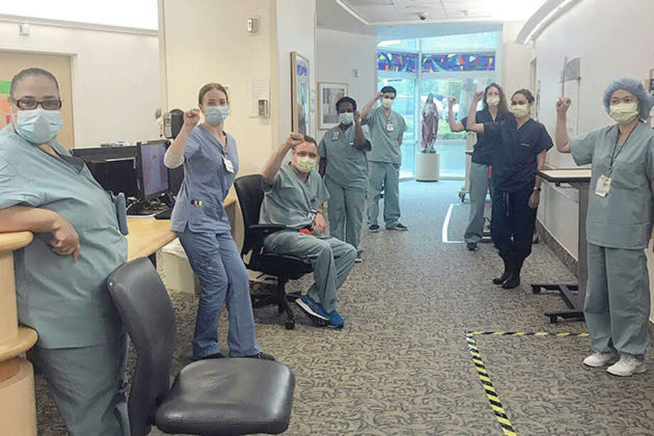 Nurses raise their fists in solidarity after telling managers they can't care for COVID-19 patients without respirator masks to protect themselves. Photo: Lizabeth Baker Wade | Via AP