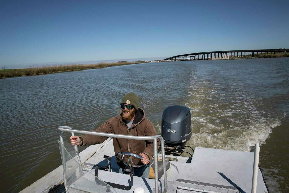 Nathan Jurisich, a fourth-generation oyster harvester based in Empire, Louisiana, steers his boat towards his family's oyster beds Friday, Feb. 28, 2020, in Empire.
