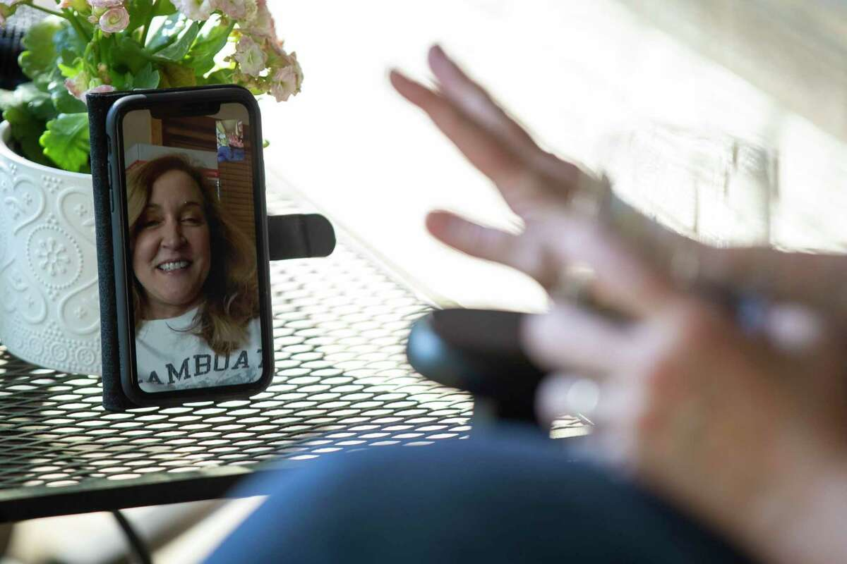Kathryn Herlich talks with her college friend Anne Curry, who lives in Colorado, from the front porch of her home in San Antonio, Texas, March 25, 2020. Shelter-in-place orders have made seeing and keeping in touch with friends and family members more challenging but Herlich and her family has been using technology such as Zoom, FaceTime and other apps.