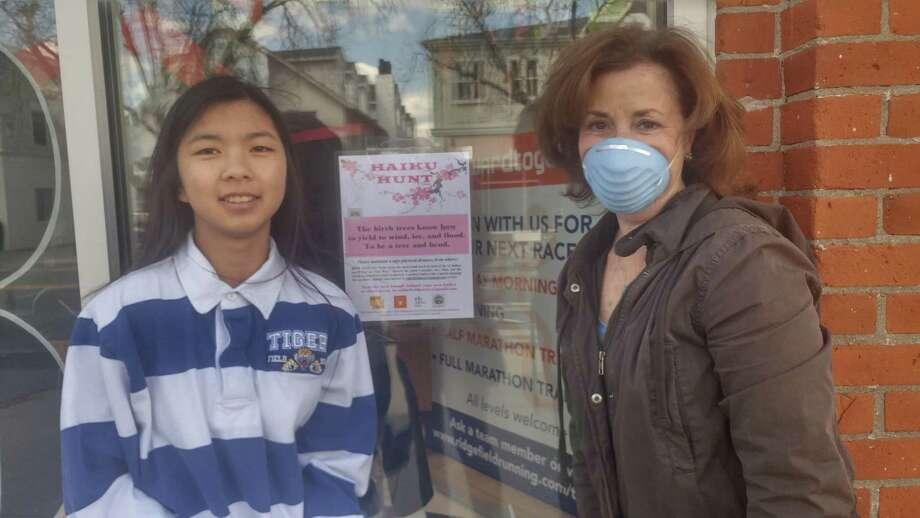 """Ariana diLaura and her mother, Jennifer, a Ridgefield Arts Council member spent an afternoon hanging """"hint"""" posters for the Haiku Hunt currently underway downtown. The activity was designed to get families out of the house and into the fresh air. Photo: Contributed Photo"""