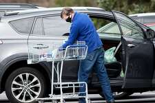 A shopper at the Village Market, wearing a protective mask and gloves, places groceries into his car on Sunday, April 5, 2020 in Wilton, Connecticut. Grocery stores have become one of the most essential businesses to remain open during the coronavirus outbreak. A shopper at the Village Market, wearing a protective mask and gloves, places groceries into his car on Sunday, April 5, 2020 in Wilton, Connecticut. Grocery stores have become one of the most essential businesses to remain open during the coronavirus outbreak.