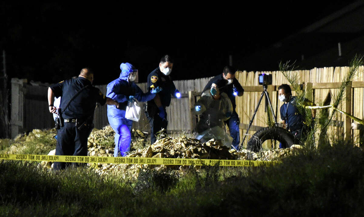 Investigators and the Webb County medical examiner assess the area behind the 4500 block ofVanesitaCt., Thursday, Apr. 16, 2020, where a dead body was reportedly found.