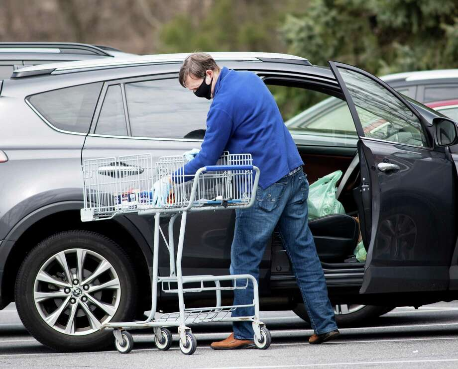 A shopper at the Village Market, wearing a protective mask and gloves, places groceries into his car on April 5. Photo: Bryan Haeffele / Hearst Connecticut Media / Hearst Connecticut Media