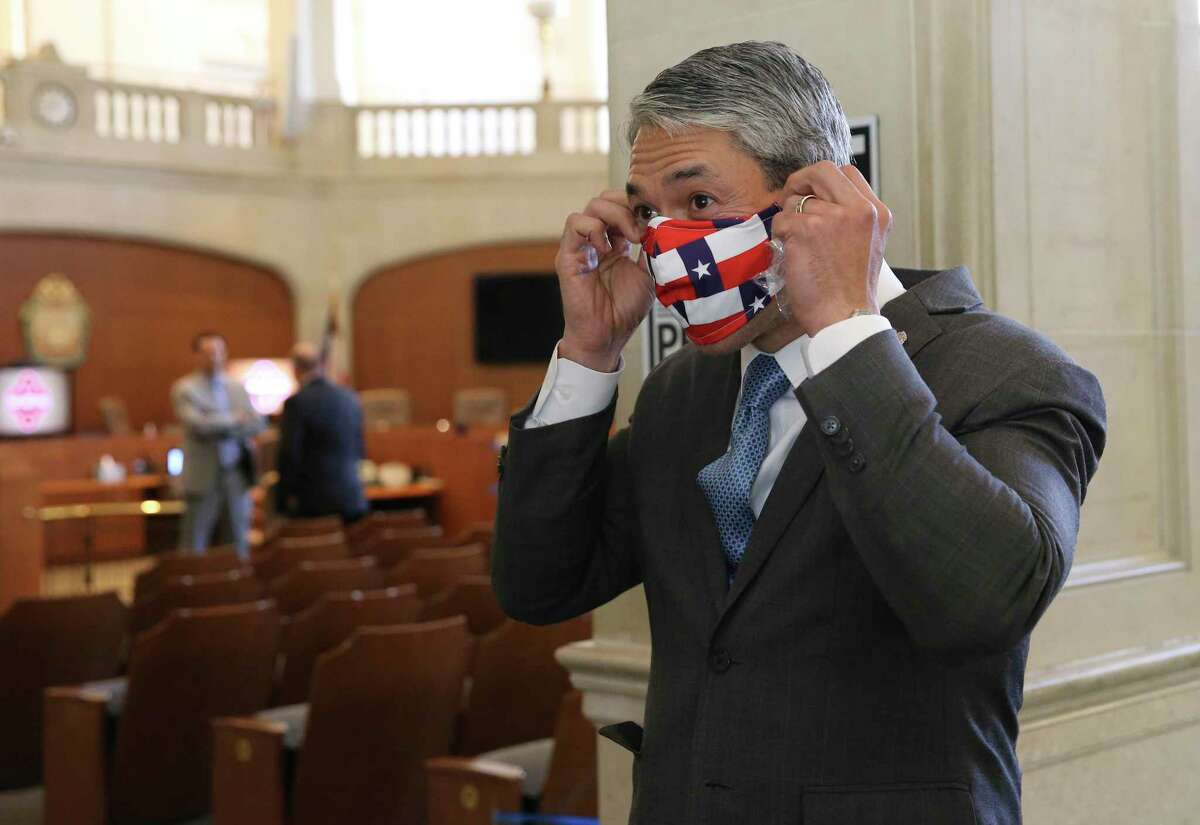 Mayor Ron Nirenberg puts on a mask after meeting with the press at the conclusion of the San Antonio City Council meeting on April 16. Nirenberg and County Judge Nelson Wolff have imposed a temporary curfew on social gatherings from 10 p.m. to 5 a.m. in public and private over the Thanksgiving holiday weekend.