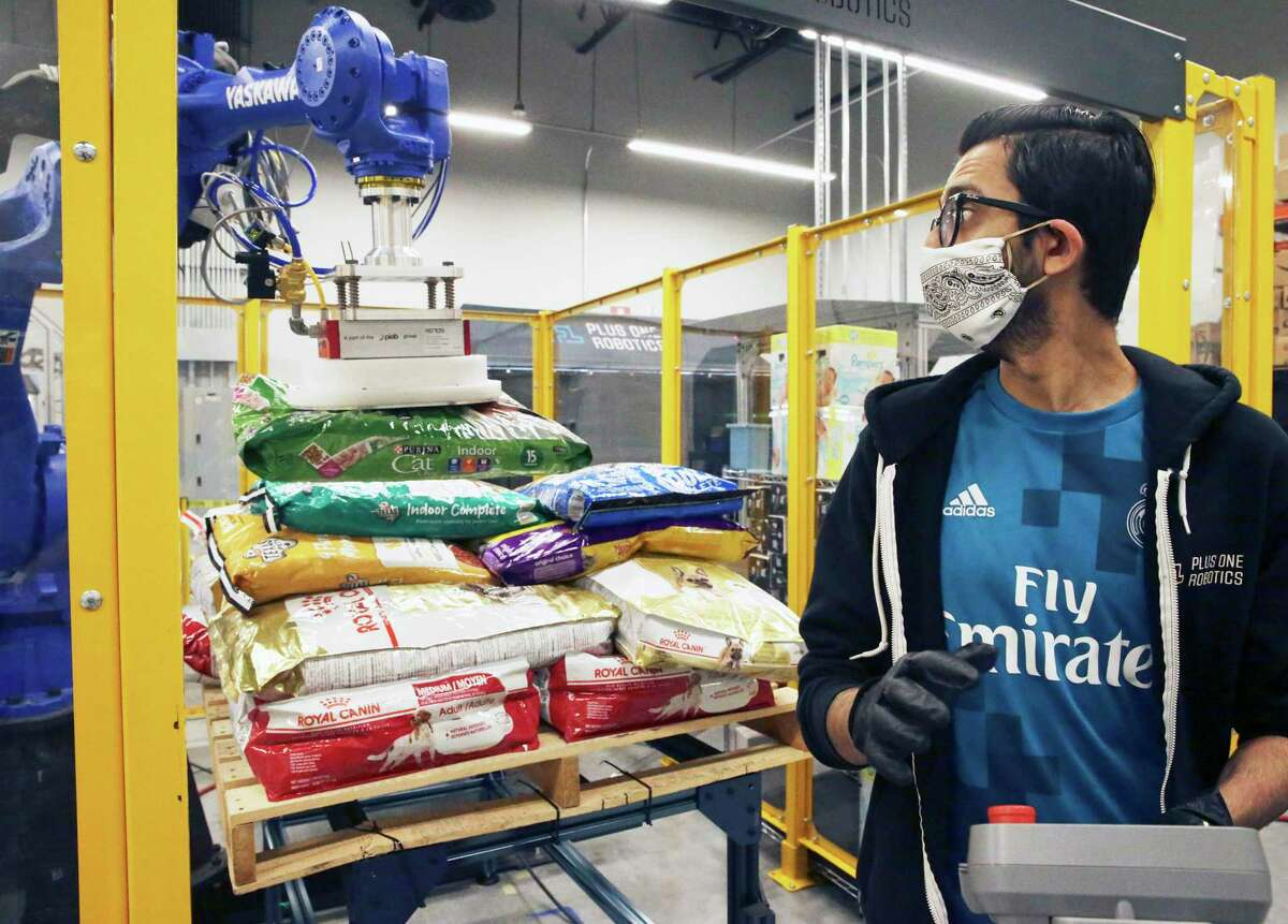 Large bags of dog food are moved by a machine that uses suction to lift controlled by Maulesh Trivedi. Plus One Robotics employees are fine tuning the warehouse robots.