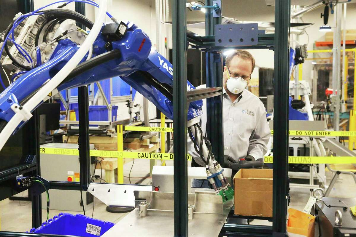 David Brain watches a machine move a box as Plus One Robotics employees work on tuning operations of warehouse robots on April 16, 2020.