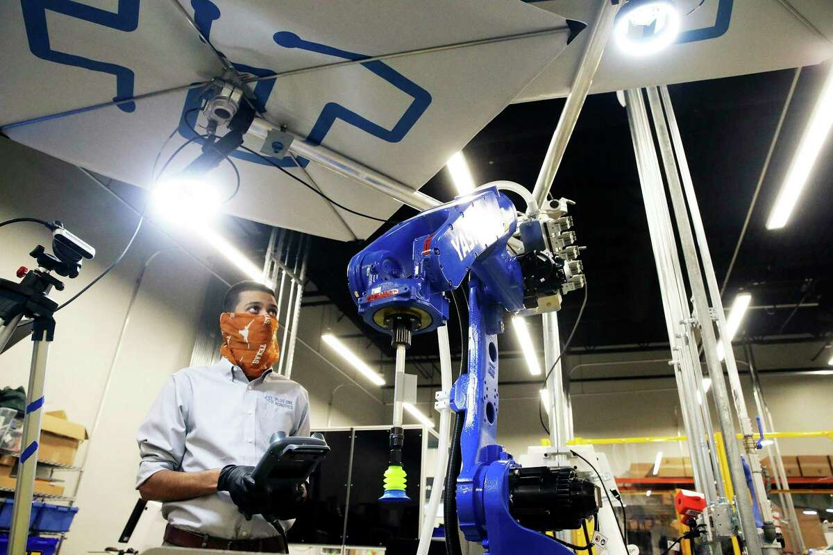 Zohair Naqui checks the positioning of lights over a machine as Plus One Robotics employees work on tuning operations of warehouse robots on April 16, 2020.