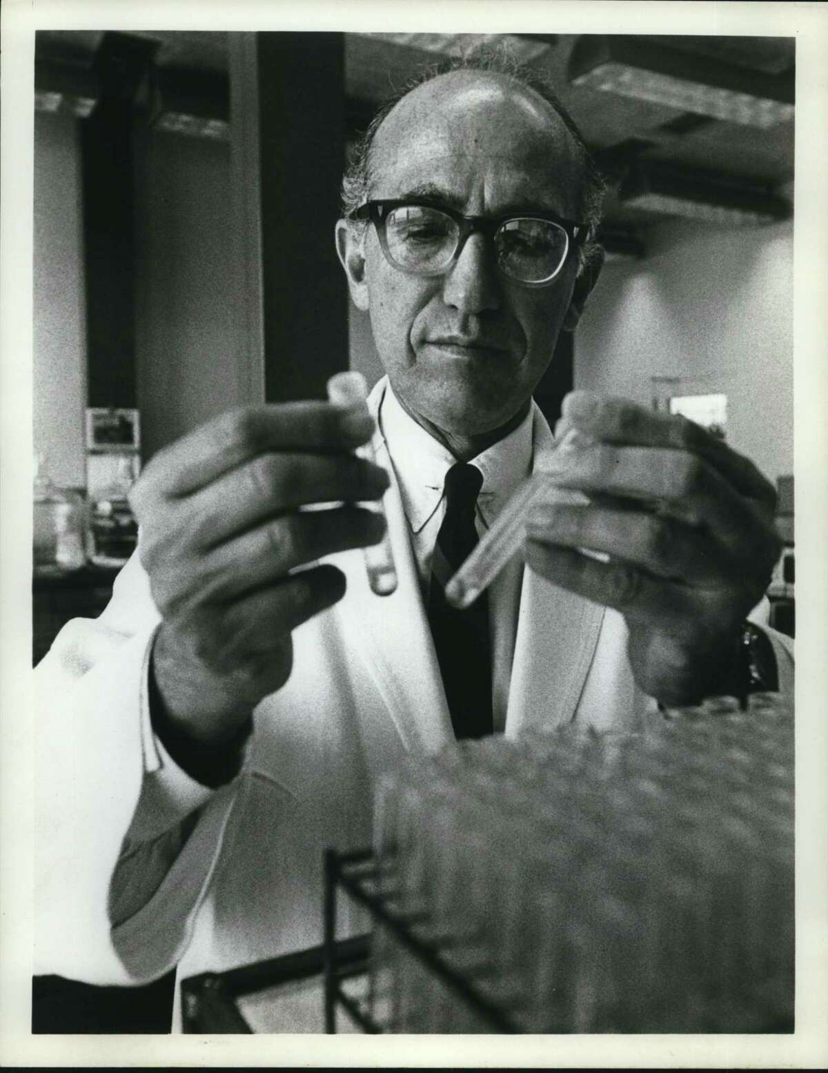 Dr. Jonas Salk conducting an experiment in his laboratory. Salk developed a vaccine for polio that was eventually distributed in Montgomery County.