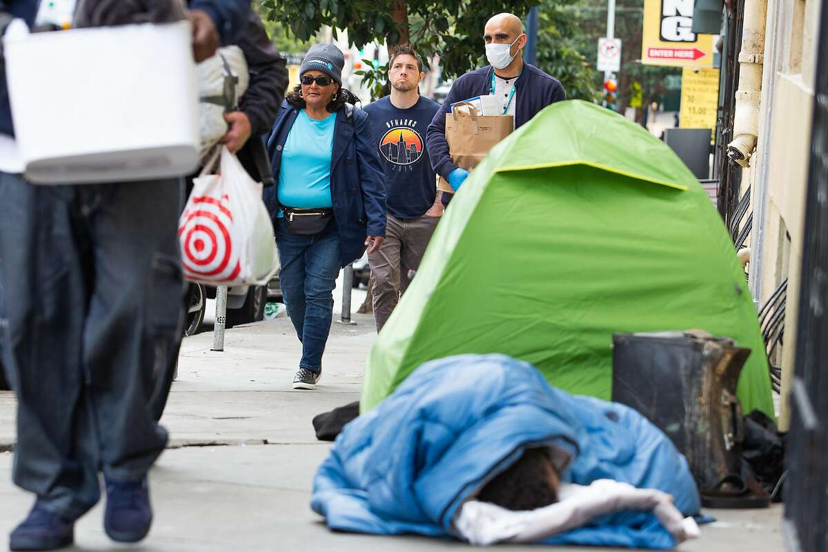 """Rachel and Michael Haynes, members of the houseless community, pass by another man experiencing homelessness on their way to their new temporary housing which St. Anthony's has paid for in order to get more """"senior"""" houseless folks off the streets during the corona virus epidemic."""