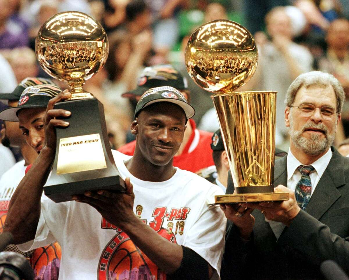 SALT LAKE CITY, UNITED STATES: In this 14 June 1998 file photo, Michael Jordan (L) holds the NBA Finals Most Valuable Player trophy and former Chicago Bulls head coach Phil Jackson holds the NBA champions Larry O'Brian trophy 14 June after winning game six of the NBA Finals with the Utah Jazz at the Delta Center in Salt Lake City, UT. The Bulls won the game 87-86 to take their sixth NBA championship. Jackson left the Bulls following the 1998 season and 12 January reports indicate that Jordan plans to announce his retirement at a 13 January news conference in Chicago. AFP PHOTO/FILES/Jeff HAYNES (Photo credit should read JEFF HAYNES/AFP via Getty Images)