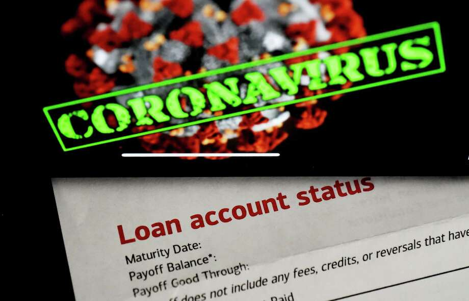"""In this photo illustration, a loan statement account status is displayed next a iPhone screen behind reading """"coronavirus"""" on April 16, 2020, in Arlington, Virginia. - The $349 billion cap for small business loans for the coronavirus stimulus was reached on April 16, 2020, taking less than two weeks to run out. (Photo by Olivier DOULIERY / AFP) (Photo by OLIVIER DOULIERY/AFP via Getty Images) Photo: OLIVIER DOULIERY / AFP Via Getty Images / AFP or licensors"""