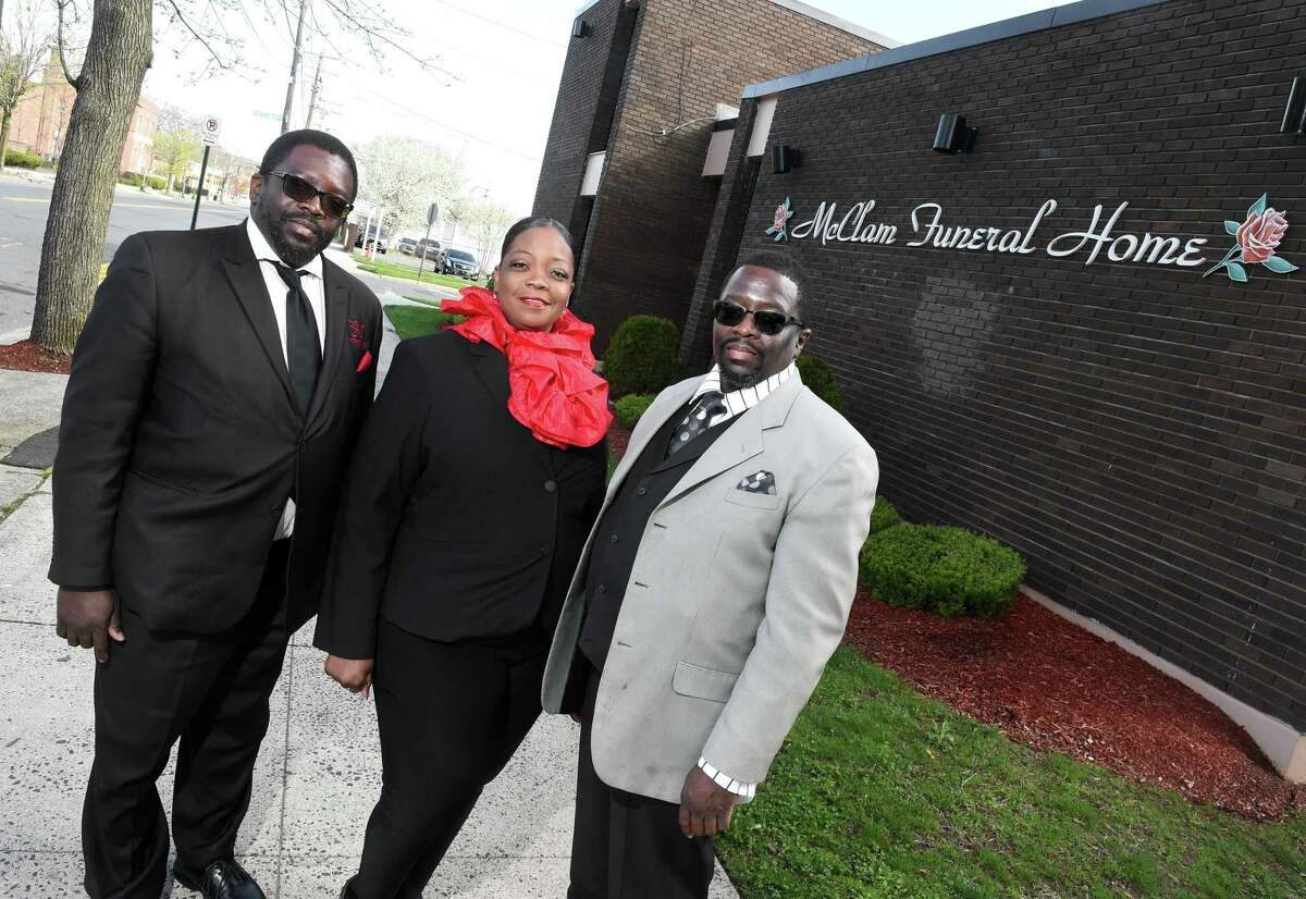 From left, siblings Darrell, Shawneeque and Darnell McClam photographed in front of their business, McClam Funeral Home, on Dixwell Avenue in New Haven on April 14, 2020.